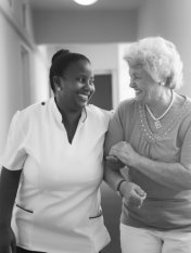 senior woman and her caregiver walking on the hall