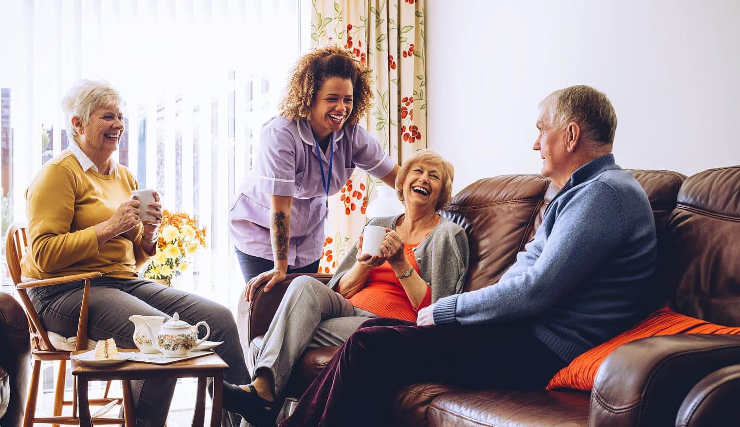 caregiver along with seniors chilling on the living room